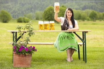 junge frau auf der wiesn zum oktoberfest mit maß bier