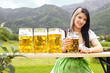 junge Frau im Dirndl in den Bergen mit Maß Bier