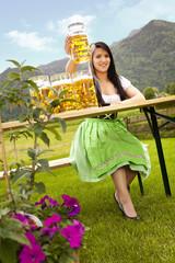 junge bayerische Frau auf der Wiesn am Biertisch mit Maß