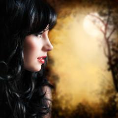 attraktive schwarzhaarige Frau vor Vollmondhintergrund