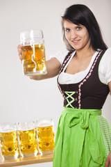 junge Frau prostet zu mit Maß Bier im Maßkrug