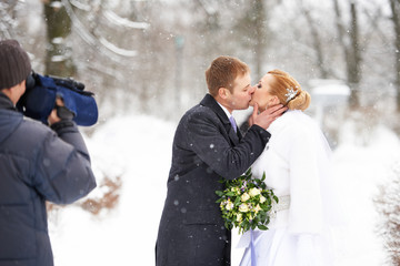 Operator shooting romantic kiss happy bride and groom