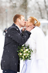 Romantic kiss happy bride and groom on winter