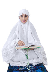 Asian female muslim reading Kuran - isolated