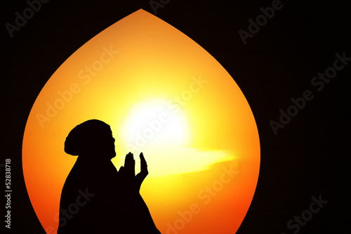 Beautiful orange silhouette of muslim praying at mosque