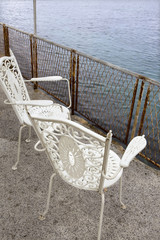 Two white chairs overlooking the water