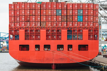 Back of a red container ship in a harbor