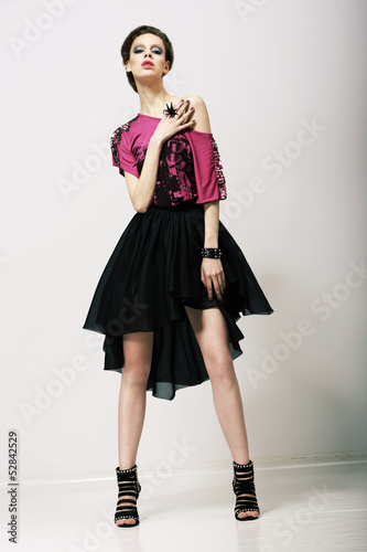 Tendency. Fashion Model in Modern Clothes posing in Studio