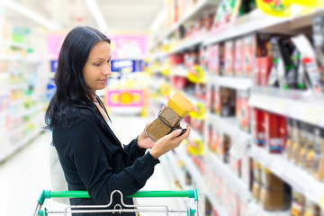 A woman buys in the supermarket coffee