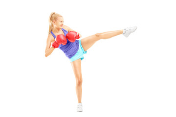 Female with boxing gloves hitting with her leg
