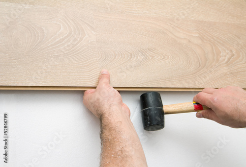 Worker installing laminate floor using a hammer