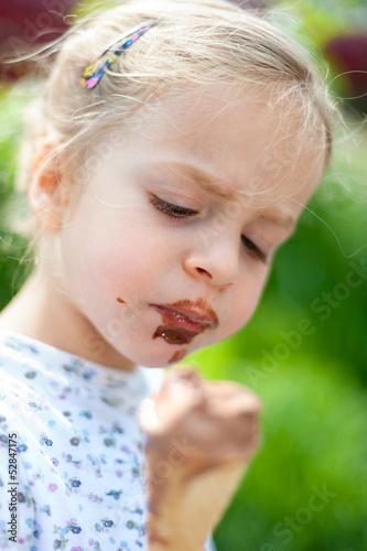 Kleines Mädchen nascht Schokoladeneis
