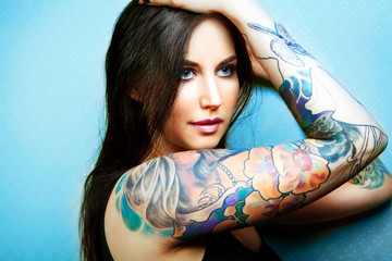 Beautiful girl with stylish make-up and tattooed arms