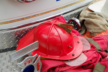 Red Fireman helmet and gear on firetruck bumper