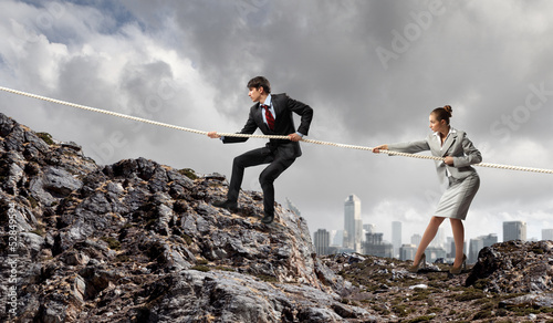 Two businessmen pulling rope atop of mountain