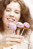 Girl with wonderful smile holding cake pops