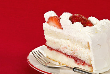 Slice of homemade strawberry cream cake against red background