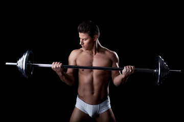 Portrait of handsome sportsman lifting weights
