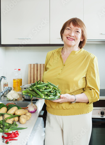 Smiling  woman cooking vegetables with okra