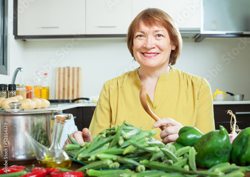 woman cooking vegetables in domestic kitchen