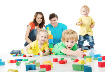Happy family. Parents, three kids playing blocks toys
