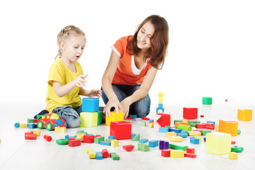 Mother and child playing blocks toys over white