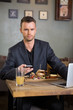 Businessman With Mobilephone And Laptop Having Sandwich