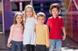Children Standing Arms Around In Kindergarten