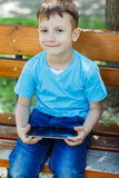 Happy boy sitting on bench with tablet