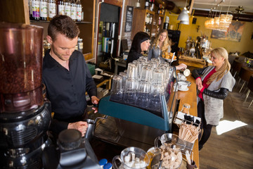 Bartender Working At Counter While Female Colleague Serving Coff