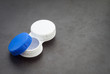 Open contact lens case on dark background.