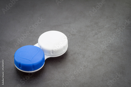 Contact lens case on dark background.