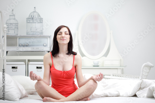 beauty girl in lotus pose indoors