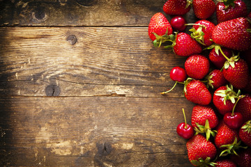 Strawberry and cherry on the old brown wooden background.