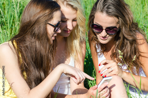 Three happy teen girl friends and mobile phone