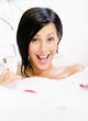 Woman taking a bath with suds and rose petals