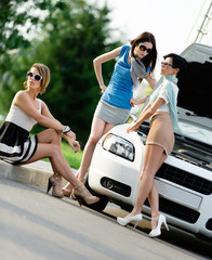 Group of three girls near the broken car with the opened hod