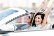 Female friends driving car with the hands up and having fun