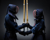 Two kendo fighters with shinai opposite each other