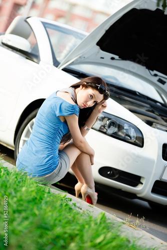 Woman sits on the grass near her broken car