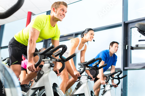 Poster group doing sport Spinning in the gym for fitness