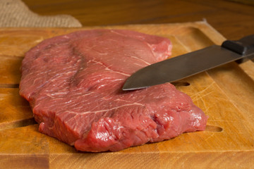 Raw beef steak on cutting board with knife