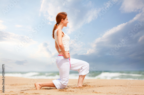 athletic woman performing a kick in an sand beach