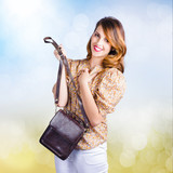 Young retro fashion model holding leather handbag