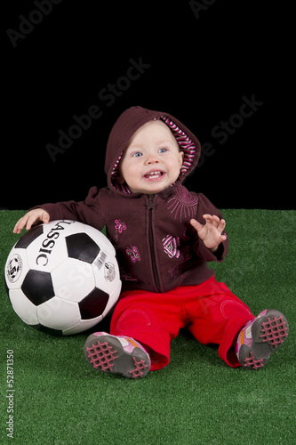 Photo shows a baby with a football
