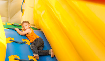 Young boy playing in an inflatable slide