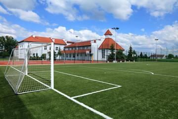 Boisko sportowe w tle państwowa szkoła podstawowa.