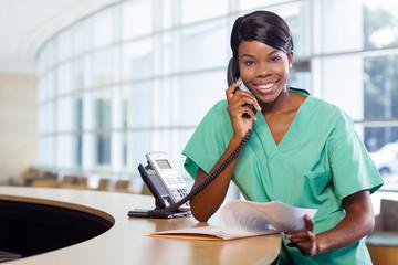Smiling nurse at work station