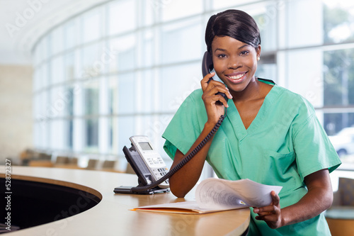 Smiling nurse at work station