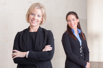 Two business women standing in hallway